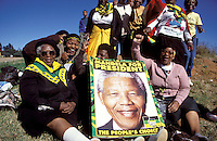 ©ÊJon Spaull / Panos Pictures..Soweto, SOUTH AFRICA..ANC supporters with a poster of Nelson Mandela at a rally prior to the country's first multiracial elections in April 1994.