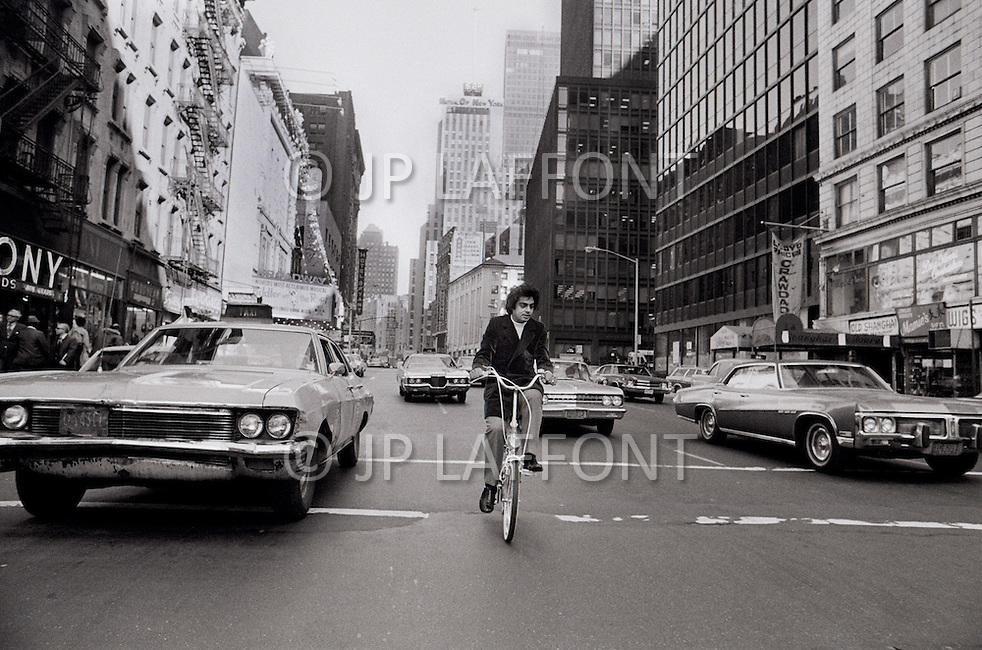 New York City, USA. October 1st, 1971. Enrico Macias rides a bicycle on Broadway and 49th street in New York City.