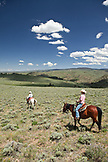 USA, Wyoming, Encampment, a cowboy and cowgirl ride through an endless landscape, Abara Ranch