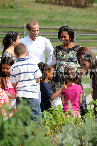 United States First Lady Michelle Obama and chef Dan Barber speak with children working in the herb garden as she tours Stone Barns Center Pocantico Hills, New York on Friday, September 24, 2010 with a large group of other First Ladies visiting New York for the United Nations General Assembly. They viewed the mobile chicken coop and herb garden while making a tour of the facilities.  A lunch was prepared with the food from the farm. .Credit: Andrea Renault / Pool via CNP