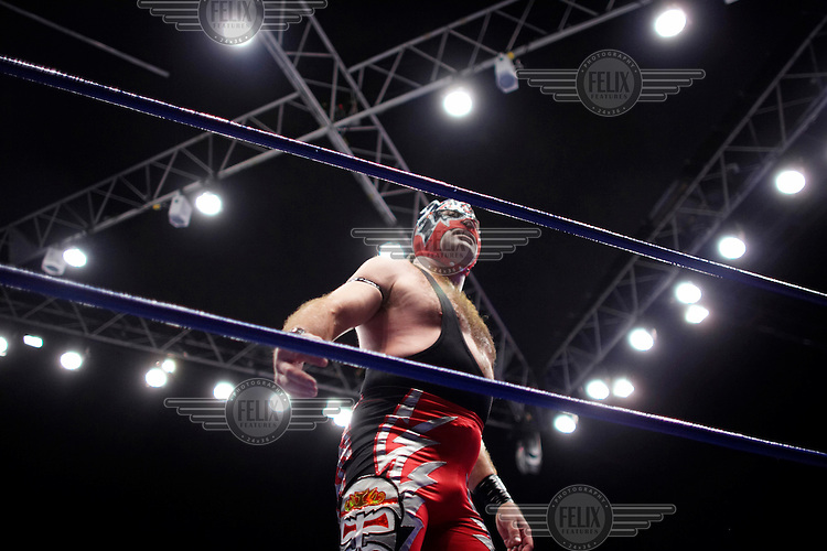 A Luchador (fighter) faces the crowd. Lucha Libre is a style of wrestling started in Mexico in 1933. The name means Free Fight, and matches tend to be focussed on spectacle and theatre with fans cheering for their favourite characters, who wear masks while jumping from the ropes, flipping opponents, and occasionally crashing into the crowd..