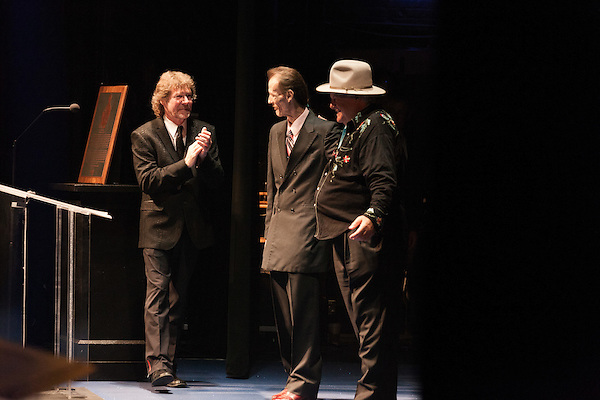 September 26, 2013. Raleigh, North Carolina.<br />  Tony Rice, center, takes the stage to accept his induction into the International Bluegrass Music Hall of Fame. He is flanked by Sam Bush, left, and Ricky Skaggs.<br />  Bluegrass guitar legend Tony Rice was inducted into the International Bluegrass Music Hall of Fame during the International Bluegrass Music Awards, held in Memorial Hall at the Duke Energy Center for the Performing Arts.