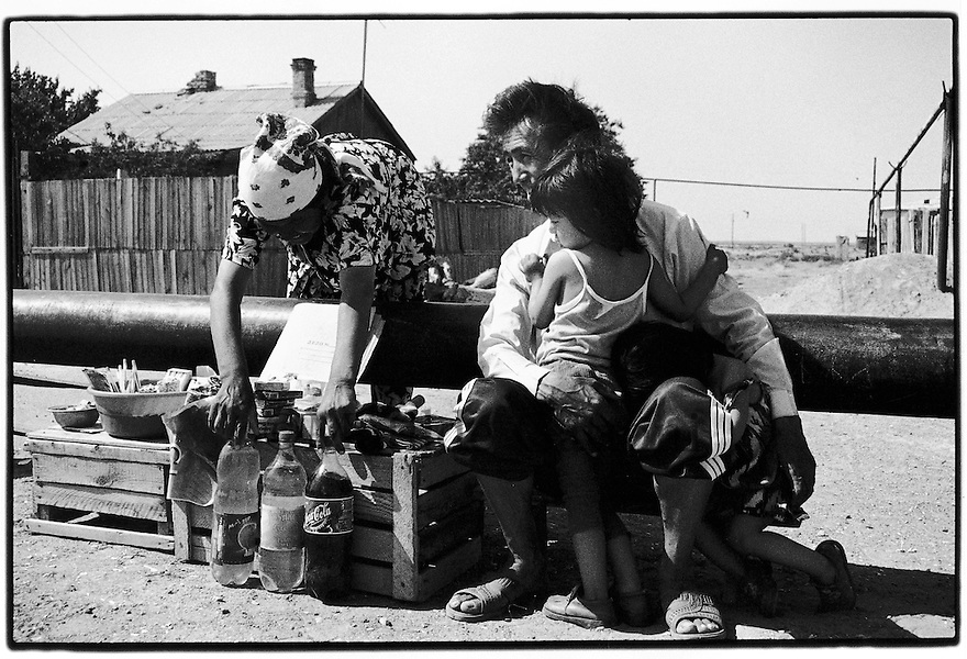 Uzbekistan - Aral Sea, Muynak - A father and his two daughters selling boiled water collected from the ponds.