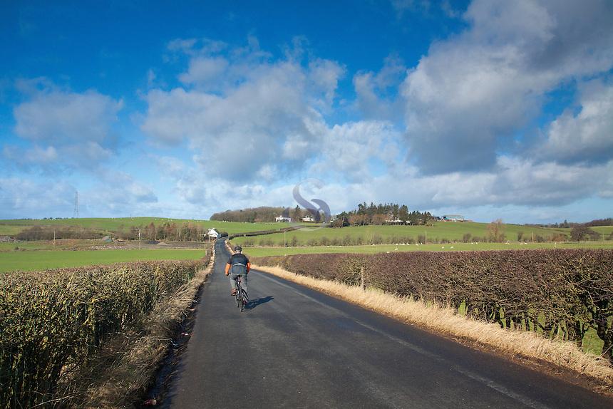 A cyclist cycling towards Thortonhall, South Lanarkshire