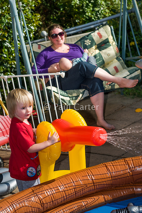 A mother breastfeeds her baby while sitting in her garden swing seat, watching her older boy spraying his father with a water canon.<br /> <br /> Taken - 27/04/2011<br /> Hampshire, England, UK