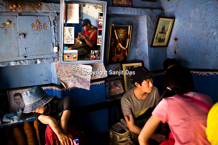 Korean tourists sit around and wait for glass of lassi (yogurt drink) at The Blue Lassi shop in the ancient city of Varanasi in Uttar Pradesh, India. Photograph: Sanjit Das/Panos
