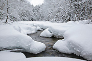 The snow covered Swift River in Waterville Valley, New Hampshire during the winter months. This river runs along the side of the Kancamagus Highway (route 112).