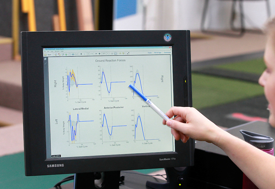 Biomechanical analyst Leigh Allin points to graphs showing the ground reaction forces captured by 3D imaging of runner Matt Clay during a visit to the UVA SPEED clinic in Charlottesville, VA. Photo/Andrew Shurtleff