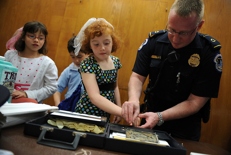 """Sophia Ayoud, 8, gets fingerprinted by Capitol Police Officer Howard Liebengood as brother Gabriel, 8, and Amina, 8, wait their turns during """"Kid Safety Day,"""" held in Dirksen, April 24, 2008.  The triplets are children of Laura Ayoud of the Senate Legislative Counsel."""