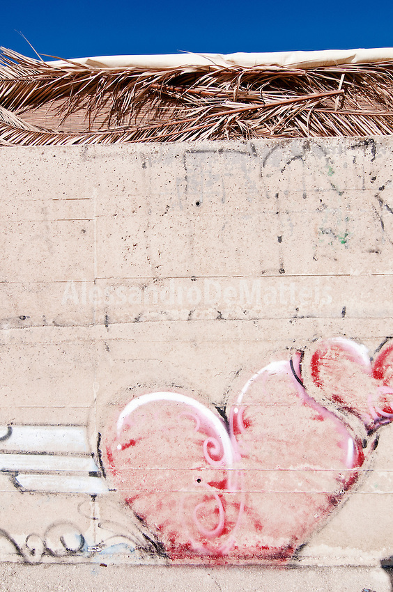 Castro Marina - Salento - Puglia - Adolescenti hanno disegnato dei murales sul muro in cemento della banchina. Alle spalle la copertura in paglia del bar della spiaggia.