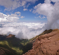 At a pullout  on the gravel road up Pike's Peak, near Colorado Springs, CO, at approximately 12000 feet altitude, the cloud layer below us appears to wash up in waves against the red rock ridges in the foreground. August 2006. clouds, cumulus, cumulonimbus, cloudbank, Colorado, mountains, sky, landscape, scenery, vacation, travel
