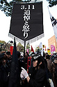 March 11, 2012, Tokyo, Japan - A woman dressed in black and holding a banner that says: to mourn for somebody makes me angry. Many protesters carrying banners took to the streets of Tokyo to demonstrate against nuclear power on the first anniversary of the Great East Japan Earthquake. (Photo by Rodrigo Reyes Marin/AFLO) (JAPAN)