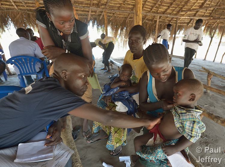 Nurse Edema Gaspar examines a child in an outreach clinic in the Rhino Refugee Camp in northern Uganda. As of April 2017, the camp held almost 87,000 refugees from South Sudan, and more people were arriving daily. About 1.8 million people have fled South Sudan since civil war broke out there at the end of 2013. About 900,000 have sought refuge in Uganda. <br /> <br /> The clinic was sponsored by Global Refuge International, which receives support from the Global Health Program of The United Methodist Church. <br /> <br /> Because of the nature of the Rhino Camp, where refugees are spread out over a wide area, it's not possible for many of them to access health care, so Global Refuge International holds outreach clinics on a regular basis through several areas of the camp.