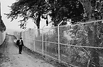 A schoolboy on his way to school passing a razor wire topped security fence  which stretched for close on a mile around the site. At the time it looked pretty shocking  people had never seen the like before.