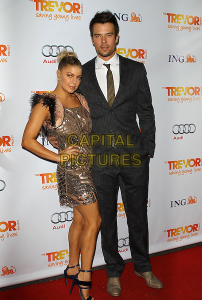 Stacy Ferguson - Fergie of Black Eyed Peas & Josh Duhamel .Trevor Live at The Hollywood Palladium in Hollywood, California, USA..December 4th, 2011.full length dress hand on hip black pink beige feathers hair up bun smiling sequins sequined black grey gray suit married husband wife .CAP/ADM/KB.©Kevan Brooks/AdMedia/Capital Pictures.