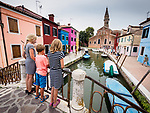 Three kids on a bridge overlook the canal, church, leaning tower in the colorful village of Burano, Italy.