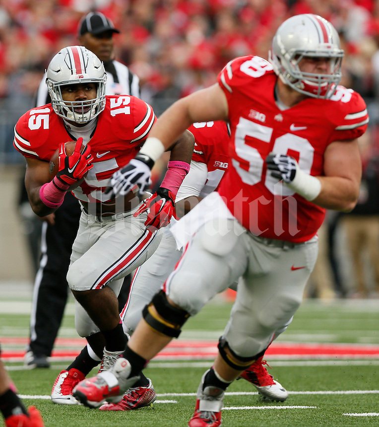 Ohio State Buckeyes offensive lineman Jacoby Boren (50) blocks for Ohio State Buckeyes running back Ezekiel Elliott (15) during Saturday's NCAA Division I football game against the Rutgers Scarlet Knights at Ohio Stadium in Columbus. The Buckeyes led at halftime 35-0. (Dispatch Photo by Barbara J. Perenic)