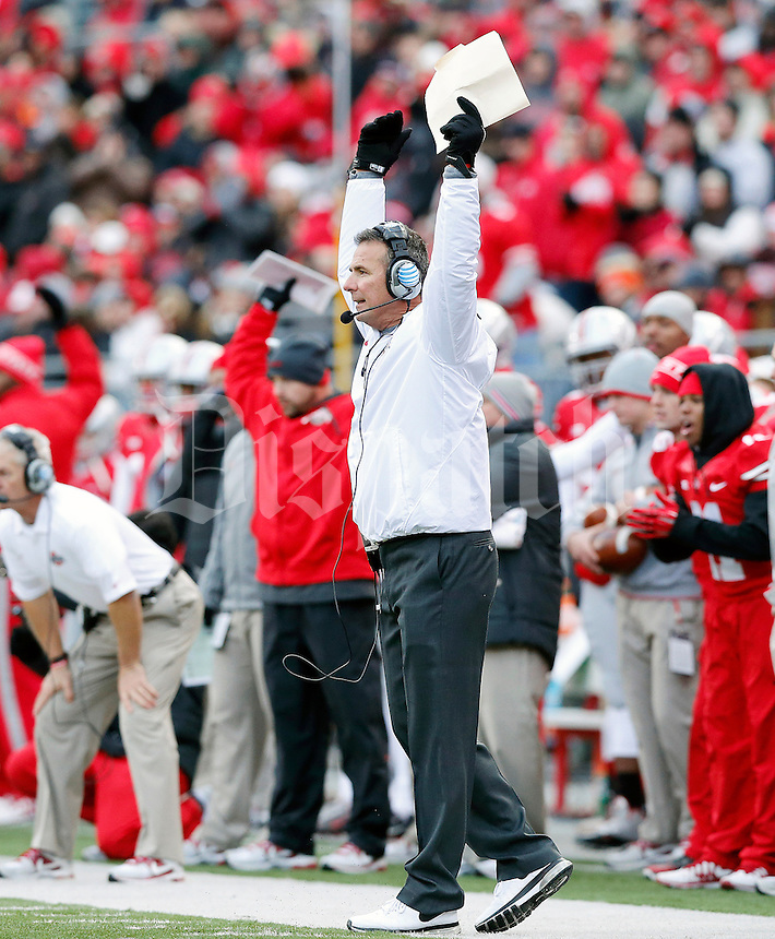 Ohio State Buckeyes head coach Urban Meyer pumps up the stadium during the first half of their College football game against Indiana Hoosiers at Ohio Stadium in Columbus, Ohio on November 23, 2013.  (Dispatch photo by Kyle Robertson)