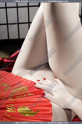 Beautiful naked asian woman covering her body with a red fan