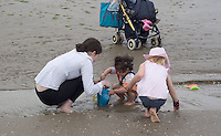 Safina being helped by Nadine to fill a bucket with sand on Bettystown beach, whilst Morgan collects shells