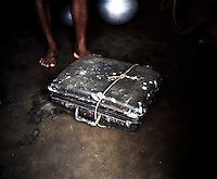 The suitcase of a Kondh family displaced by construction of the Vedanta Alumina plant. The huge bauxite deposits in the Niyamgiri hills have led the Vedanta group to set up an alumina refinery at Lanjigarh, making the local population of Dongria Kondh tribespeople fearful for their future. Vedanta Resources has come under immense pressure from human rights and environmental groups to abandon its plans to mine at the Niyamgiri mountains, as the site is considered sacred by the local tribal community...