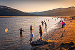 Crowds of people fishing for hooligan with nets at Twenty Mile River at sunset. Portage, Southcentral Alaska, Summer.