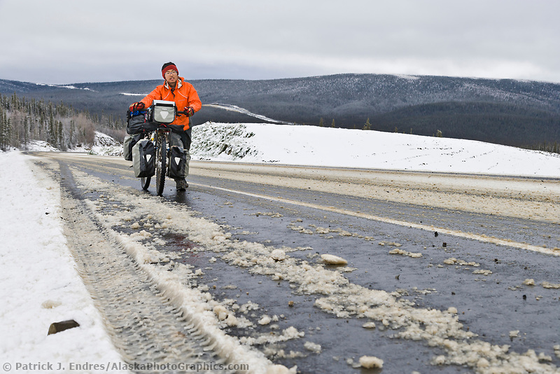 Japanese bicycle rider walks his bike up a steep hill on the James Dalton Highway