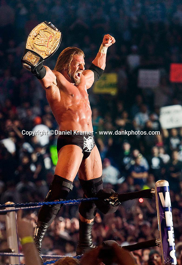 Triple H celebrates after defending his title against Randy Orton in the WWE Championship match at WrestleMania 25 at Reliant Stadium on April 5, 2009 in Houston, Texas.