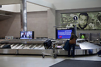 A woman pick up her baggage at the luggage carousel of the Detroit Metropolitan Wayne County Airport' MacNamara Terminal Thursday June 6, 2013. Usually called Detroit Metro Airport or simply DTW, Detroit Metropolitan Wayne County Airport is a major international airport in the United States.