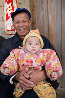 Man holds baby on his lap in Fuli Old Town, Xingping. China has a one child policy to limit population.