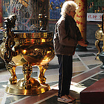 Bao-jhong Yi-min Temple, Kaohsiung -- A Taoist worshiper praying.<br /> <br /> This elder lady holds two half-moon shaped, wooden oracle chips called 'zhi jiao' in her hands.<br /> <br /> The 'zhi jiao' are used to communicate with a god. The worshiper asks the god a simple yes/no questions, and then throws the two pieces own the floor in front of him. There are three possibilities how the pieces end up: both are facing down, both are facing up, or one each faces up and down.<br /> <br /> If one piece lands face up and the other one face down, the god's answer to the question posed is affirmative. If both pieces come to lie face down the answer is 'no'.<br /> Should both pieces lie face up the god simply gives a smile. This means that he refuses to answer the question, in which case the Taoist believer proceeds to ask a similar, but slightly question until he gets an answer from the god.