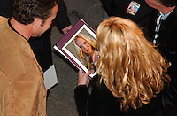 Rick Wilson Photo--2/7/04--Recording artist Mila autographs a picture of herself for a fan after singing the national anthem before the start of the Bud Shootout at Daytona International Speedway Saturday night.