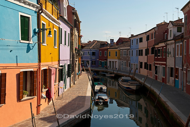 """The lagoon island of Burano is a short 40-minute trip from Venice on a """"vaporetto"""" or water bus. It is densely populated with a population of about 4,000. Burano actually consists of four individual islands, which are separated by narrow canals. The often-photographed island is known for its brightly painted houses."""