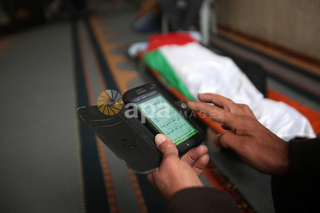 A man reads the Koran near the body of Palestinian Rahiq Birawi, who according to the Israeli police was shot dead after she had advanced towards them with a knife in her hand at a checkpoint last October, during her funeral after Israel released her body, in the West Bank village of Aseera Ashamaliya near Nablus December 17, 2016. Photo by Nedal Eshtayah