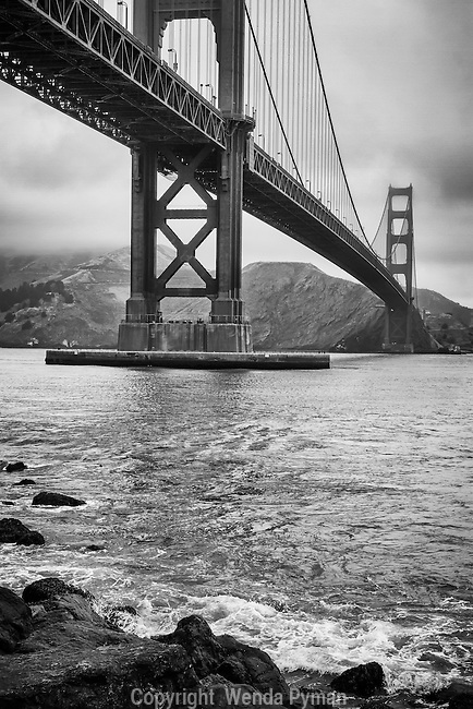 Foggy morning with both Golden Gate Bridge Towers; low tide surf beating on the rocks along the shore.