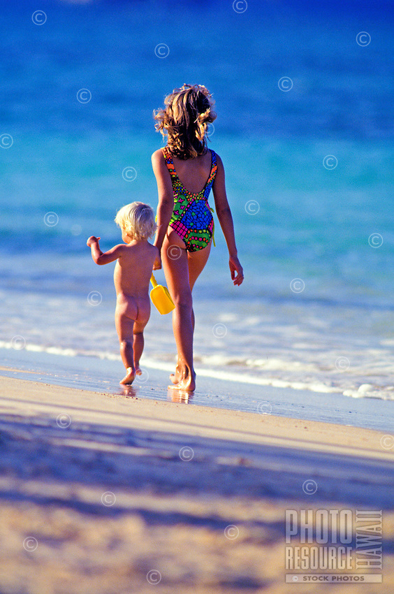 A small blond, bare toddler holds the hand of his nine year old sister in a swimsuit as they walk along the shore at Lanikai Beach.