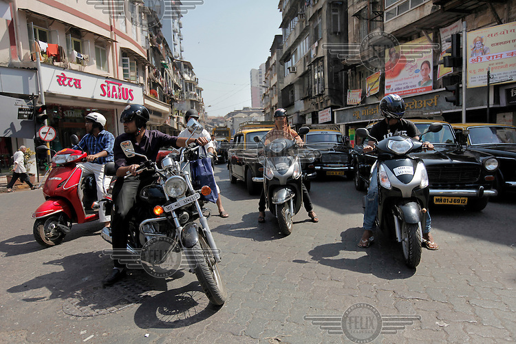 Group of motorcyclists wait for green light  at a junction in central Mumbai.