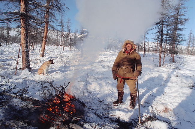 Andrey Oporka, an Even reindeer herder warms himself by an open fire at winter pastures. N.Evensk, Magadan, E. Siberia, Russia