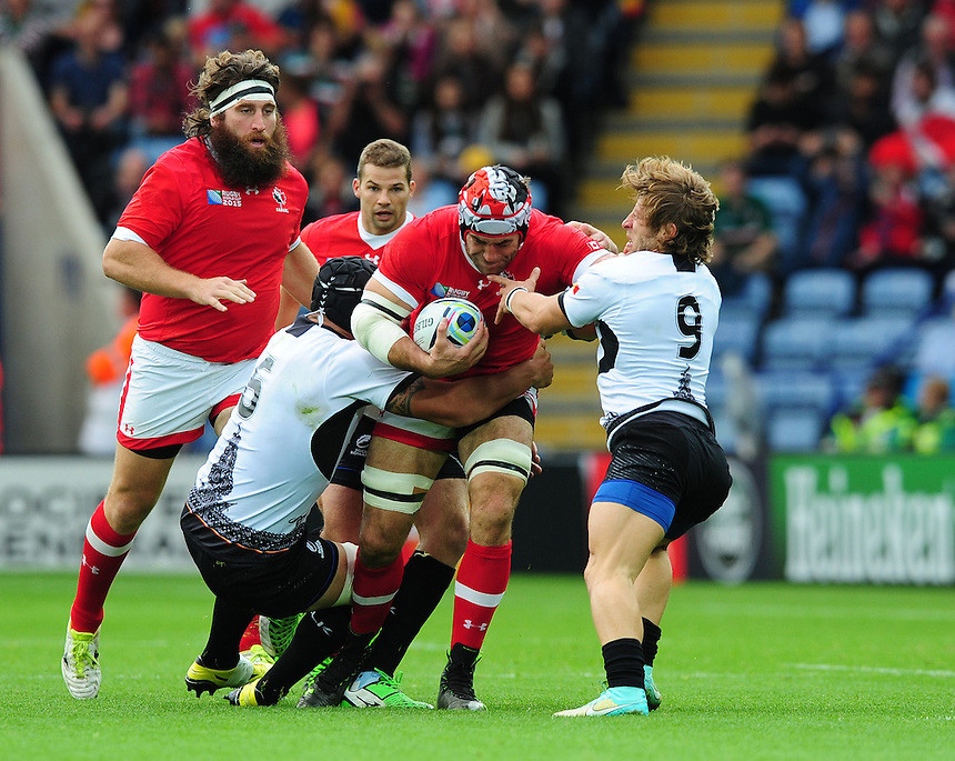 Canada's Jamie Cudmore is tackled by Romania's Valentin Ursache, left, and Romania's Florin Surugiu<br /> <br /> Photographer Chris Vaughan/CameraSport<br /> <br /> Rugby Union - 2015 Rugby World Cup Pool D - Canada v Romania - Tue 6 October 2015 - King Power Stadium, Leicester <br /> <br /> &copy; CameraSport - 43 Linden Ave. Countesthorpe. Leicester. England. LE8 5PG - Tel: +44 (0) 116 277 4147 - admin@camerasport.com - www.camerasport.com
