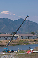 Mount Fuji behind a crane that will empty lift a box containing fifteen thousand rubber ducks before emptying them in to the Sakawa River during the Ashigara River festival, Kintaro duck-race in Matsuda, Kanagawa, Japan April 25th 2010