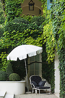A sun-lounger under a parasol occupies a sheltered ivy- clad corner of the garden