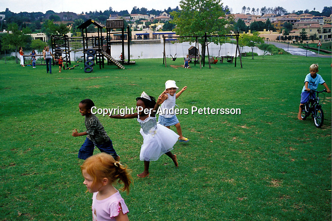 JOHANNESBURG, SOUTH AFRICA - FEBRUARY 29: Lebone Dube, age 4, playing with her friends at her birthday party on February 29, 2004 in Cedar Lake, a up-market gated community in Johannesburg, South Africa Her father, Oscar Dube, works as a Key Account manager for the Swedish mobile phone equipment maker Ericsson and his wife, Mpho Dube, is fund manager at Old Mutual, an insurance company in SA. They belong to the new black elite in SA. Lebone attends an exclusive pre-school with mostly white children and she invited them for her birthday party. Well educated and connected, they have risen from the poverty in the townships to a very different lifestyle, since the fall of Apartheid and the start of democracy in the country in 1994. .Photo: Per-Anders Pettersson/iAfrika Photos....