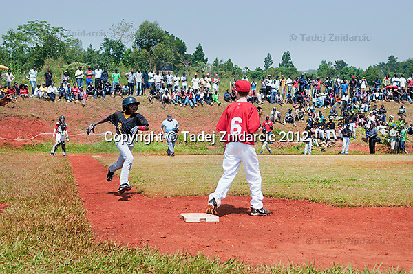 Ugandan player Jonathan Kizza runs towards the first base during the game in Mpigi, Uganda on January 17 2012 between Ugandan Little League team and Canadian Little League team from Langley.