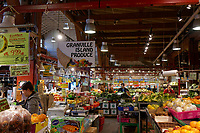 People shopping for fruit and produce inside the Granville Island Public Market, Vancouver, British Columbia, Canada