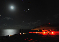 Sailors view a full moon over the Pacific Ocean from the flight deck aboard USS Abraham Lincoln.
