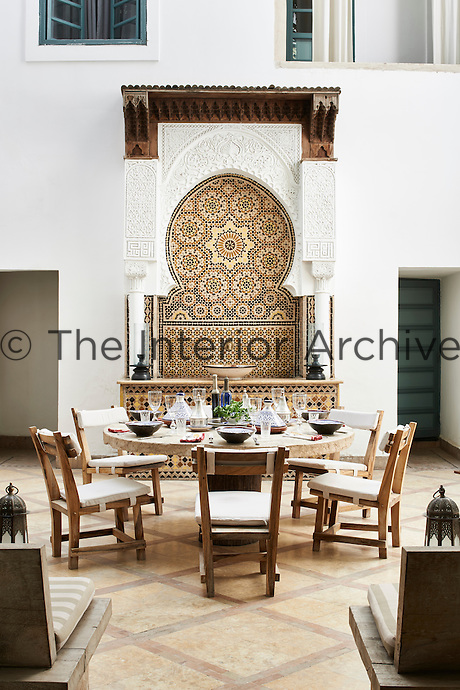 A round stone table is laid for an alfresco lunch on the courtyard patio. On one side, a decorative Moorish mosaic tiled panel is set behind a table.