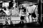 Taken through a restaurant window of girl with open mouth talking to friends. South Beach Miami Florida 1999 .