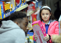 Pictured: A young girl looks at Nathan Dyer Wednesday 08 December 2016<br />Re: Swansea City FC players have bought Christmas gifts for 60 children at Smyths toy store in Swansea, south Wales.
