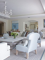 Two comfortable armchairs upholstered in the palest of eggshell blue are arranged next to the matching sofas in the living room