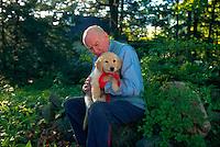Senior man holding his golden retriever puppy.